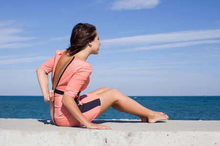 Girl at the sea  Girl unzips pink dress sitting on seashore Standard-Bild