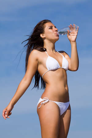 Barefoot young woman in white swimwear drinking water standing against of sky photo