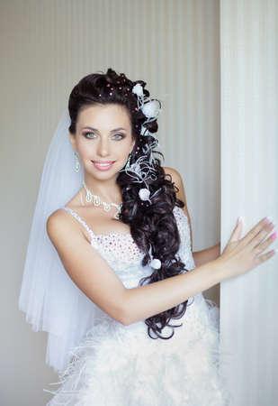 Aantrekkelijke bruid tegen de muur Bruid poseren kijken naar de camera glimlachen