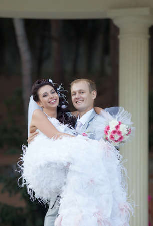 Newly wedded couple in the park  Just married in day of their wedding  Фото со стока