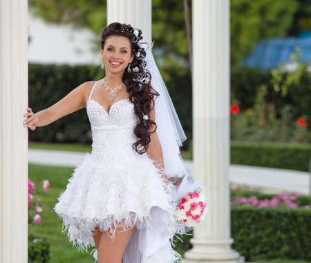 Aantrekkelijke bruid in het park Bruid poseren kijken naar de camera glimlachen