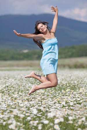 Young woman jumping high in wide chamomile field Banque d'images