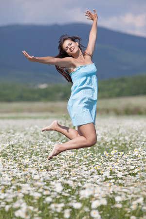 Jonge vrouw springen hoog in brede kamille veld