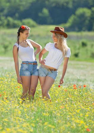 Twee zusters in het veld Twee jonge vrouw in korte broek poseren in medow Stockfoto