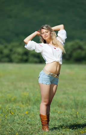 Girl in shorts in field  Attractive blond woman in shorts posing in field Stock Photo