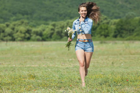 Girl in shorts in field  Teenage girl with bouquet of wild chamomile running along field