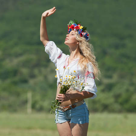 Ukrainian girl in field  Attractive blond woman in ukrainian wreath and blouse with ukrainian embroidery posing on open air Standard-Bild