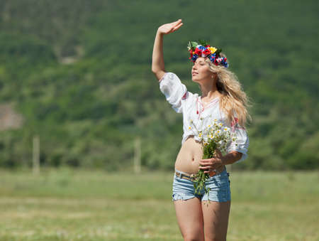 Ukrainian girl in field  Attractive blond woman in ukrainian wreath and blouse with ukrainian embroidery posing on open air taking bouquet of wild chamomile Standard-Bild
