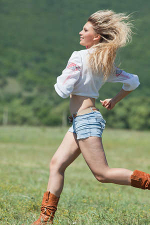 Ukrainian girl in field  Attractive blond woman in blouse with ukrainian embroidery running along field  Vertical composition photo