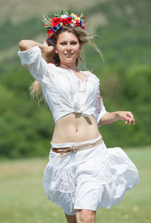 Ukrainian girl in field  Attractive blond woman in ukrainian wreath and blouse with ukrainian embroidery running along field  Vertical composition