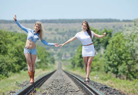 Two sisters outdoors  Two young women are walking along railway photo