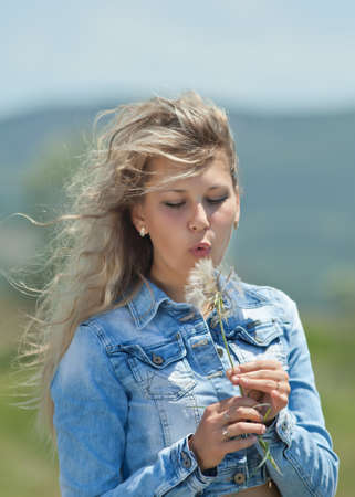 Portrait of blond girl outdoors  Attractive young woman blowing on fetus of wild flower like a dandelion photo