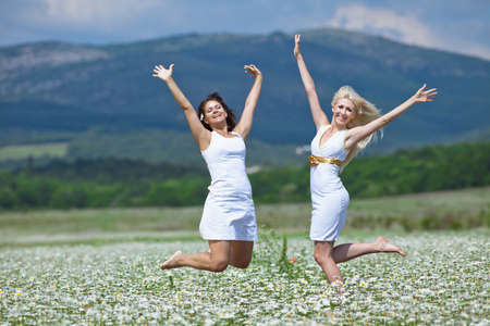 Attractive young women jumping in chamomile field with raised hands  Jumping girls photo