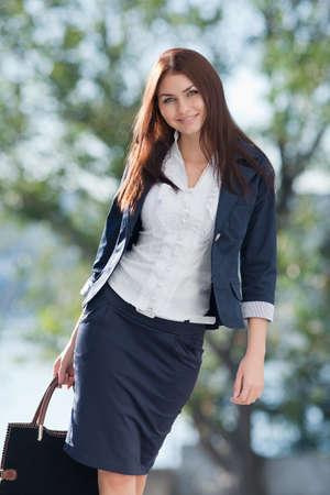 Aantrekkelijke langharige brunette op de open lucht Jonge zaken vrouw loopt naar camera