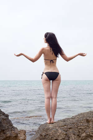 Young woman at the sea  Attractive brunette in bikini posing in full back position Stock Photo