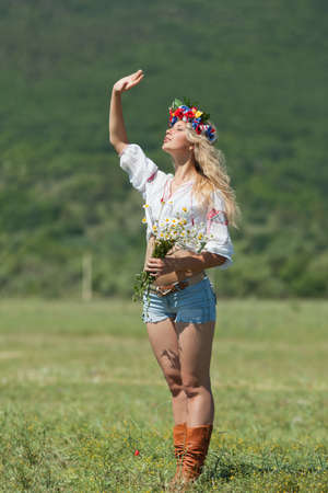 non moving activity: Ukrainian girl in field  Attractive blond woman in ukrainian wreath and blouse with ukrainian embroidery posing on open air Stock Photo