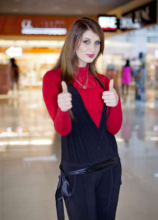 Long haired girl at the mall  Attractive brunette in red and black showing thumbs up looking at camera  Stock Photo - 17500268