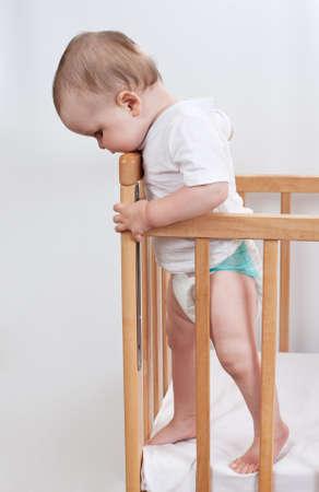 Charmant kind in de wieg Charming baby staat in kind bed en naar beneden te kijken