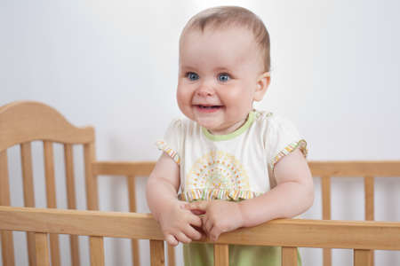 handrails: Charming child in the crib  Charming baby holds the handrails and laughs