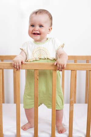 6 12 months: Charming child in the crib  Charming baby holds the handrails and laughs