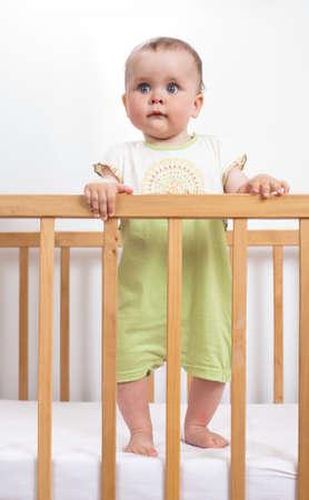 rompers: Ni�o con encanto en el pesebre del beb� con Encanto sostiene el pasamanos y se r�e