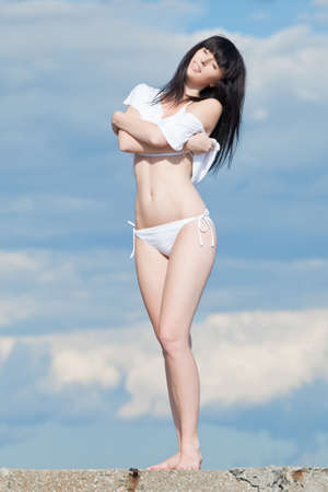 Brunette in white  Attractive young woman in white on background of cloudy sky photo