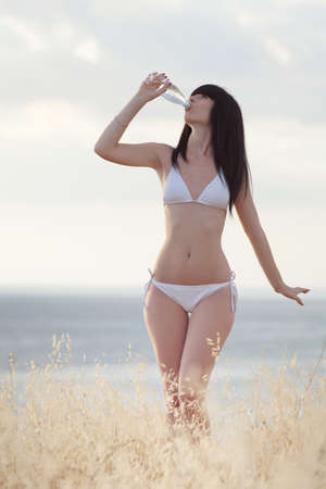 Brunette in white on open air  Attractive young woman in white on seashore photo