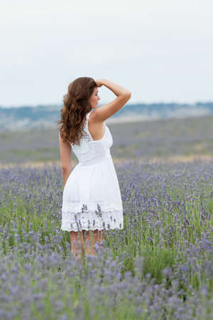 Young woman in white outdoors  Attractive girl in the field of blossoming lavender photo