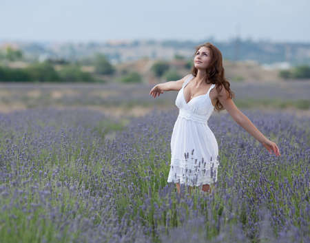 arms  outstretched: Young woman in white outdoors  Attractive girl in the field of blossoming lavender