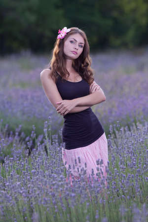 singlet: Young woman posing outdoors. Attractive girl in the field of blossoming lavender Stock Photo