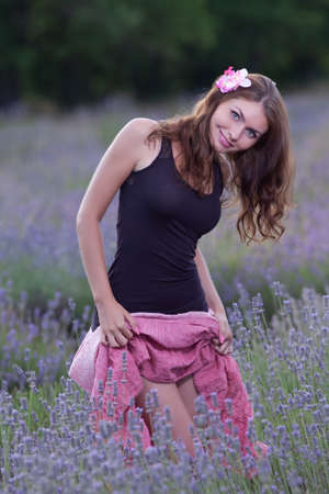 bowed head: Young woman posing outdoors. Attractive girl in the field of blossoming lavender Stock Photo