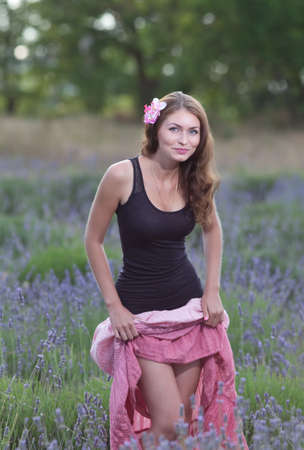 skirt up: Young woman posing outdoors. Attractive girl in the field of blossoming lavender Stock Photo