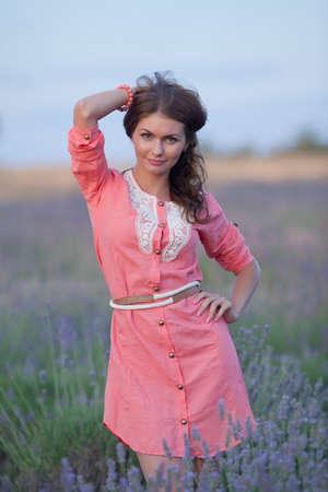 Jonge vrouw op het gebied van bloeiende lavendel. Portret van aantrekkelijk meisje in roze jurk in het veld van bloeiende lavendel