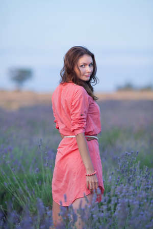 Young woman in the field of blossoming lavender. Portrait of attractive girl in pink dress in field of blooming lavender Stock Photo