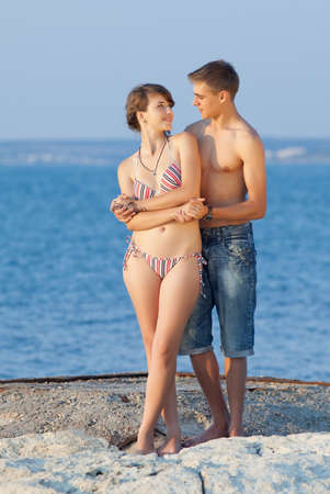 Attractive couple at the sea  Young heterosexual couple flirting at the sea in evening time photo