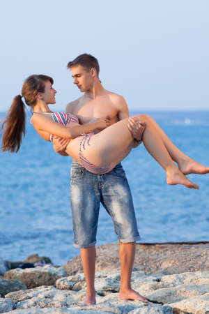 russian man: Attractive couple at the sea. Attractive guy and girl are playing at the sea in evening time