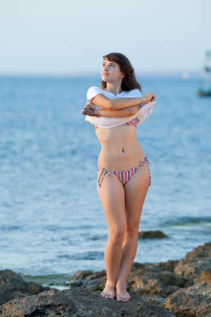 Girl undresses on rocky seashore in evening time photo