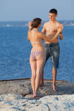 swimsuit: Attractive couple at the sea  Young heterosexual couple flirting at the sea in evening time Stock Photo