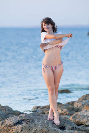 Attractive young woman at the sea  Girl undresses on rocky seashore in evening time photo