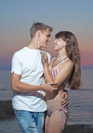Attractive couple at the sea  Young heterosexual couple flirting on seashore in evening time photo