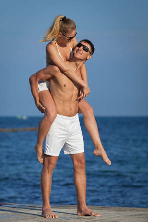 Piggyback  Attractive couple in sunglasses on background of sky photo