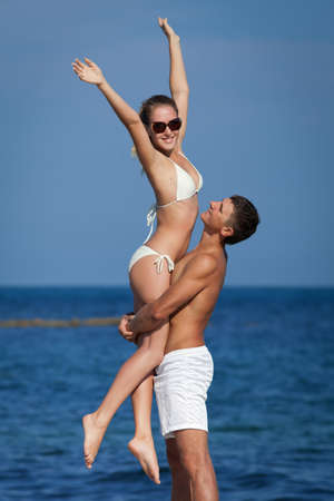 man carrying woman: Attractive couple at the sea  Young man and woman on seashore in day time Stock Photo