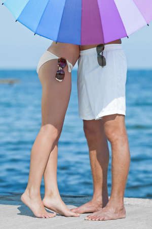 parasol: Attractive couple at the sea  Young man and woman on seashore in day time Stock Photo