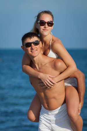 Piggyback  Attractive couple at the sea  Guy carrying on shoulders his girl at seashore in day time photo
