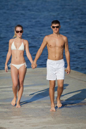 Attractive couple at the sea  Young man and woman in white swimwear and sunglasses walking along pier in day time photo