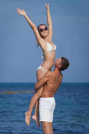 Attractive couple at the sea  Guy holding on hands his girl at seashore in day time photo