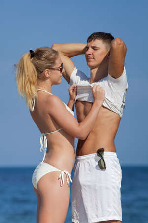 Attractive couple at the sea  Girl undressing her guy on open air in day time photo