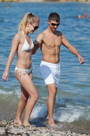 Attractive couple at the sea  Young man and woman in white swimwear and sunglasses walking along seashore in day time photo