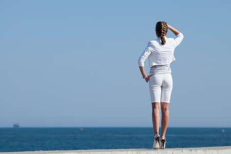 Jonge vrouw in het wit op de zee Aantrekkelijke vrouw in witte tribunes aan de kust op zoek naar afstand Achterkant