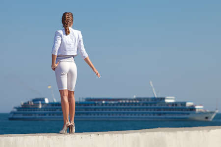 Young woman in white at the sea  Attractive woman in white observes passenger ship  Rear view photo